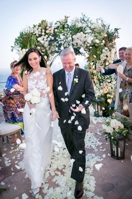 Wedding vow renewal in Santa Barbara ocean view flower petal toss by guests aisle