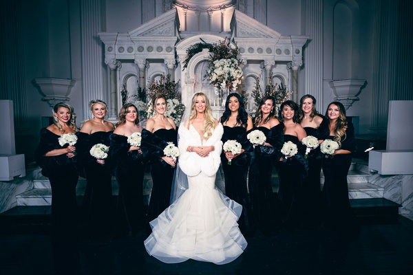 bride in mermaid wedding dress with fur wrap bridesmaids in black velvet dresses with fur wraps