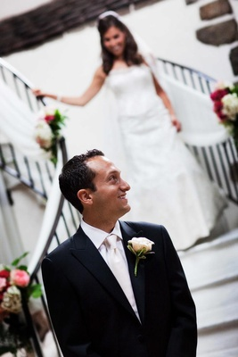Groom in white tie waits for his bride to come down the staircase