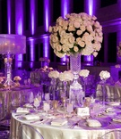 Round reception table with tall flower arrangement ivory rose and hydrangea with Ghost chairs