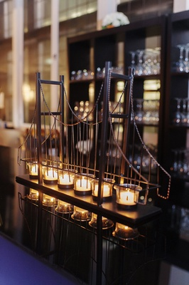 model of John A. Roebling Suspension Bridge with row of tea lights