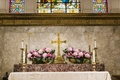 Pink flowers in gold bowls on Christian altar