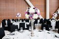 Wedding reception tall silver centerpiece with white hydrangea purple flowers round table black