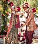 Indian bride and groom participate in Jaimala ceremony