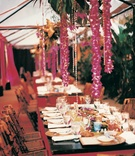 Bamboo chairs and floral garlands decorate a rustic reception