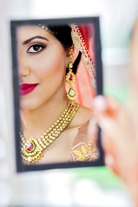 reflection shot of indian-american bride checking her makeup in the mirror