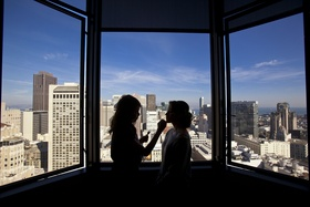 Bride getting makeup on with city skyline silhouette