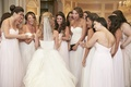 Bride with excited bridesmaids outside ceremony