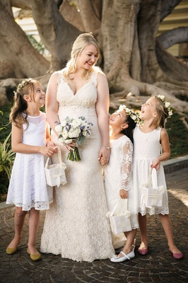 Bride in lace wedding dress with three flower girls flower crowns and lace knee length dresses