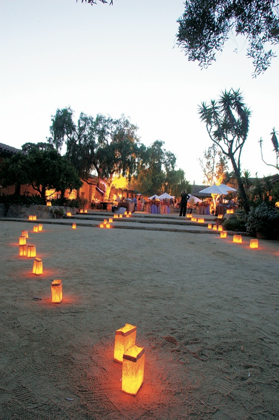 Path of paper bag lanterns in sand