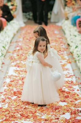 Two flower girls walk down flower petal aisle