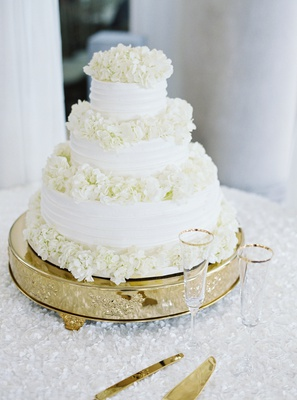 simple three-tiered white wedding cake with layers of hydrangea blooms