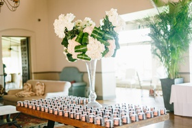 escort card table with macaron favors, floral arrangement with folded leaves
