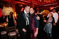 Matthew Christopher, couture wedding gown designer, in a black tuxedo with his groom at reception