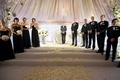 Bridesmaids in strapless black gowns and light bouquets with groomsmen in tuxedos at tented ceremony