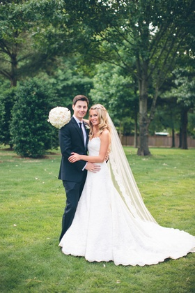 Young couple in wedding attire on grass lawn