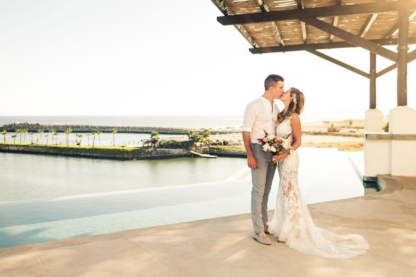 bride in lace yolancris gown, groom in dress shirt and grey slacks, cabo san lucas wedding