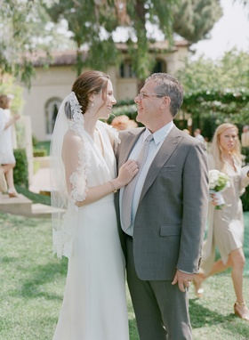 Bride in white sheath dress with father in grey suit