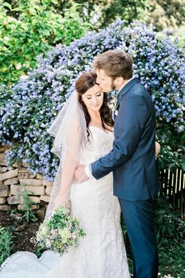 groom kissing bride forehead garden english british england wedding wildflower bouquet blue suit