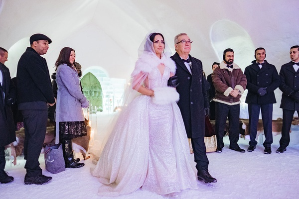 bride in sparkle wedding dress overskirt with fur hand muff and cape walking with father guest coats