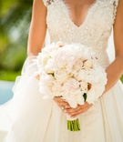 Bride in Carolina Herrera v-neck wedding dress holding bouquet light flowers white pink rose peony