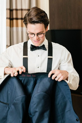 groom in bow tie glasses and suspenders holding tuxedo jacket with custom she said yes embroidery