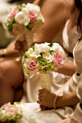 Bridesmaids sitting at ceremony holding flowers