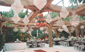 Outdoor wedding reception with crystal chandeliers hanging from wood beams