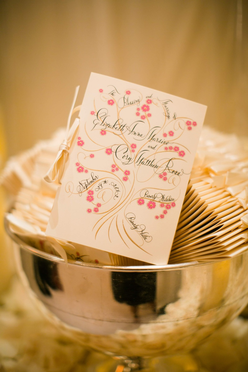 Wedding ceremony program with calligraphy and pink flowers