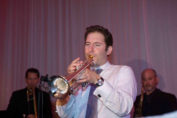 Groom in white button up and tie with trumpet