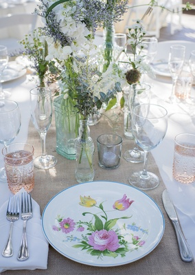 rustic burlap table runners white table linens white china with floral details glass vases candles