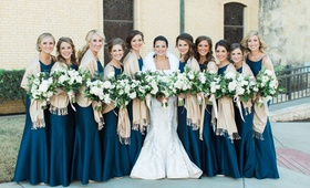 Bride in Romona Keveza wedding dress with fur wrap and bridesmaids in navy blue with champagne throw