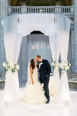 bride and groom kiss under chuppah with white pink orchid rose flowers indoor ceremony cleveland