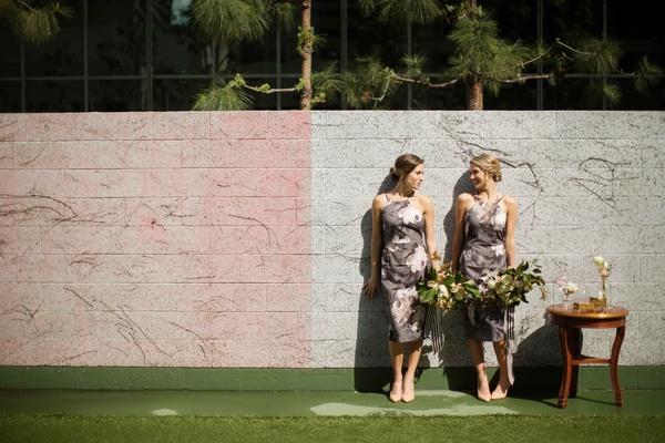 Bridesmaids in Asos dresses pose near wall