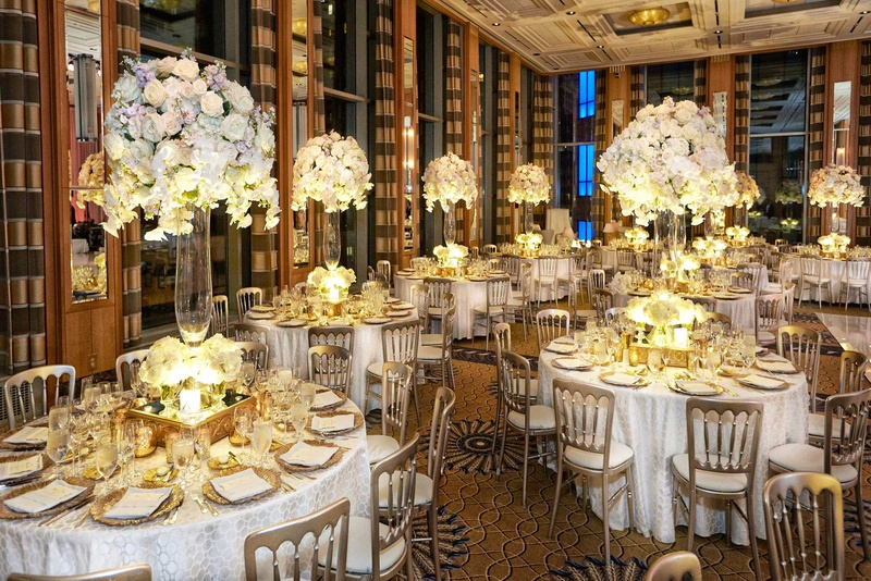 opulent tablescapes white linens gold charger plates clear glass vases tall white floral arrangement