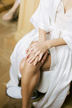 bride in white robe, pale pink manicure for wedding day, solitaire engagement ring