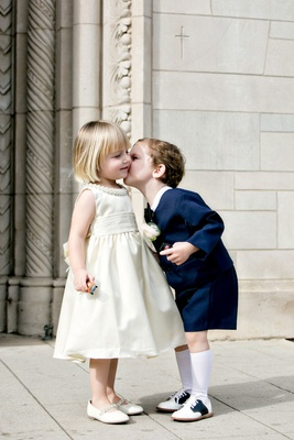 Ring bearer in short suit with bow tie and knee socks kiss flower girl on cheek in ivory dress flats