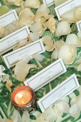 Wedding reception place cards on a green print tablecloth surrounded by petals