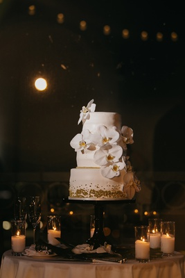 three tier wedding cake with fondant, orchids, gold pearl sprinkles