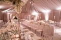 Pink tent wedding reception long tables clear chairs white flowers high low centerpieces