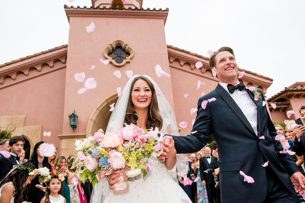 Wedding guests tossed flower petals at the bride and groom as they left the ceremony space