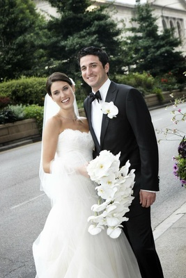 Couple holding orchid bouquet and boutonniere