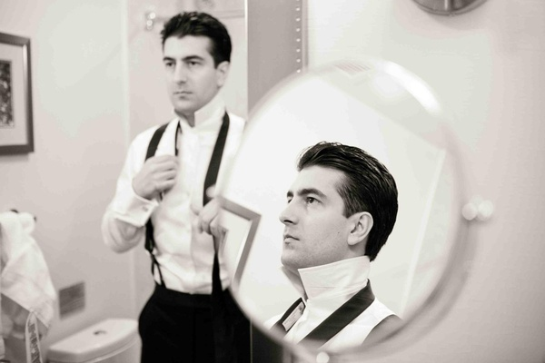 Black and white photo of groom getting ready in mirror