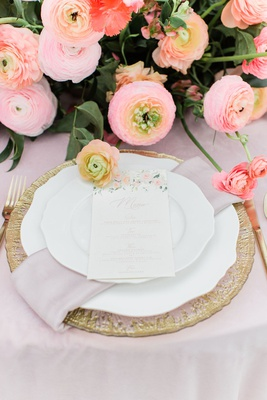 wedding reception menu placed on top of china, blush napkin, and gold charger