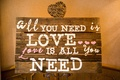 "Wedding shower sign made of wooden boards with quote ""All you need is love...Love is all you need"""