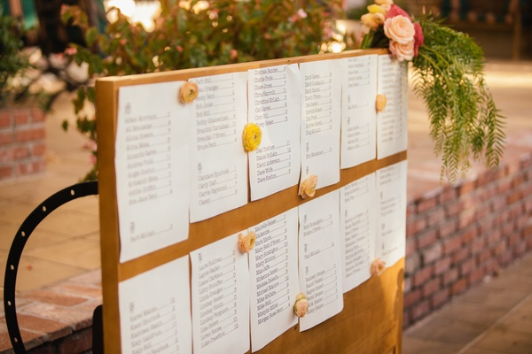 Outdoor wedding reception with a seating assigment sheets on wood board decorated with peach flowers