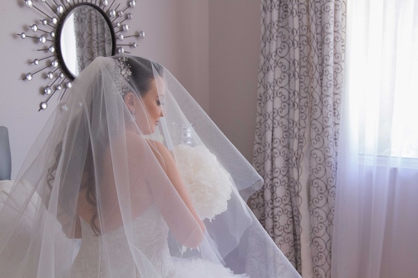 Wedding dress with mid back, beautiful veil and headpiece over long curled wedding hairstyle peonies