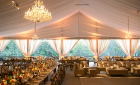 Tent wedding in Texas with chandeliers, lighting, long rustic wood tables, and low centerpieces