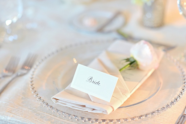 Bride escort card on top of napkin with pink rose
