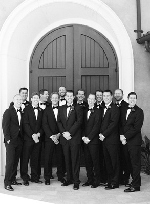 Black and white photo of groom with 12 groomsmen in tuxedos and bow ties